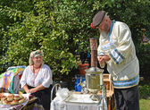 The elderly man kindles a samovar at fair of national creativity — Stock Photo