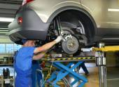 Workers establish depreciation racks on the car. Assembly convey — Stock Photo