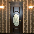 Wooden brown door with a stained-glass window and two wall lamps — Stock Photo #56949025