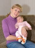 The young woman sits on a sofa with the baby on hands — Stock Photo
