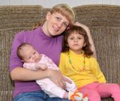 The young woman embraces the three-year-old daughter and the bab — Stock Photo
