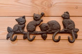 Metal hanger with hooks in the form of kittens on a wooden wall — Stock Photo