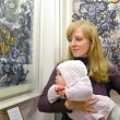 The young woman with the baby consider a picture at an exhibitio — Stock Photo #65309101