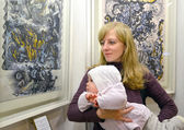 The young woman with the baby consider a picture at an exhibitio — Stock Photo