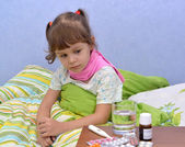 Portrait of the little sick girl sitting in a bed near drugs — Stock Photo