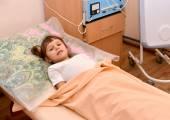 La petite fille malade se trouve sur un canapé dans un offi physiothérapeutique — Photo