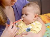 The woman gives to the sick baby medicine by means of the batche — Stock Photo