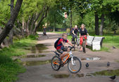 ST. PETERSBURG, RUSSIA - JULY 24, 2015: The family by bicycles goes on a path of park. Focus on the woman — Stock Photo