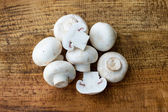 Champignon mushrooms on wooden background — Stock Photo