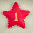 Red star with wooden number 1 on vintage fabric background — Stock Photo #58498845
