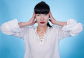 Asian woman in a white shirt posing with her hands on her head — Stock Photo