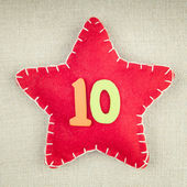 Red star with wooden number 10 on vintage fabric background — Stock Photo