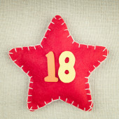Red star with wooden number 18 on vintage fabric background — Stock fotografie