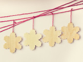 Handmade wooden snowflakes hanging on red strings — Stock Photo