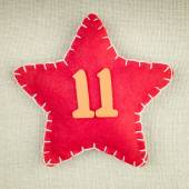 Red star with wooden number 11 on vintage fabric background — Zdjęcie stockowe