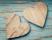 Two wooden hearts placed nicely on a turquoise vintage wood back — Stock Photo