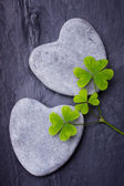 Two grey heart shaped rocks with three clovers on a tile backgro — Stockfoto
