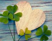 Llucky clovers with an old wooden heart on a blue vintage wood b — Stock Photo
