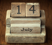 A very old wooden vintage calendar showing the date 14th July on — Foto de Stock