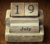 A very old wooden vintage calendar showing the date 19th July on — Stock Photo