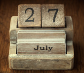 A very old wooden vintage calendar showing the date 27th July on — Stock Photo