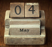 A very old wooden vintage calendar showing the date 4th May on w — Foto de Stock