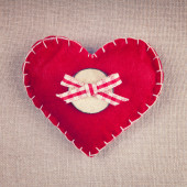 Red heart with wooden button and bow on vintage fabric backgroun — Stockfoto