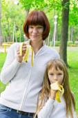 Mother and daughter eating banana — Stock Photo