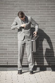 Businessman in business attire with suitcase — Stock Photo