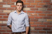 Young man against brick wall — Stock Photo