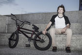 Young bmx rider sitting — Stock Photo