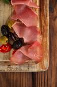 Meat platter of Cured Meat and olives on old wooden board — Stock Photo