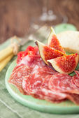 Meat platter of Cured Meat and figs on green wooden board — Stock Photo