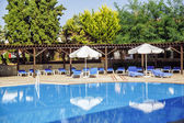 Large swimming pool with sun loungers and parasols — Stock Photo
