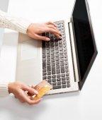 Mão de mulher insere dados usando o laptop e cartão de exploração de crédito em — Fotografia Stock