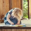 Little girl drawing with colored pencils on a country house wood — Stock Photo #53556191