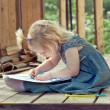 Little girl drawing with colored pencils on a country house wood — Stock Photo #53556199