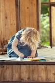 Little girl drawing with colored pencils on a country house wood — Stock Photo