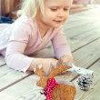 Little girl playing with Christmas decorations - reindeer and co — Stock Photo #57489603