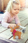 Little girl playing with Christmas decorations - reindeer and co — Foto de Stock