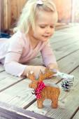 Little girl playing with Christmas decorations - reindeer and co — Photo