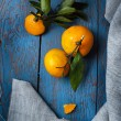 Two fresh mandarines with green leaves on wooden table — Stock Photo #65147681