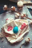 Easter decoration - wooden egg on fabric napkins, with cotton br — Stock Photo
