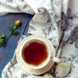 Cup of tea set with a beautiful tea towel and roses on a wooden  — Stok fotoğraf #66640811