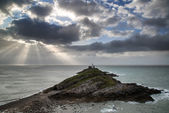 Lighthouse landscape with stormy sky over sea with rocks in fore — Stock Photo