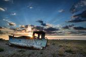 Abandoned fishing boat on beach landscape at sunset — Stock Photo