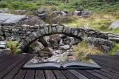 Old ancient packhorse bridge over mountain stream in Autumn conc — Stock Photo