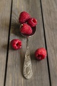 Raspberries in rustic kitchen setting with wooden background — Stock Photo