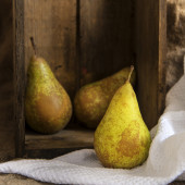 Pears in rustic kitchen setting with wooden box and hessian sack — Stock Photo