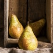 Pears in rustic kitchen setting with wooden box and hessian sack — Stock Photo #66869053